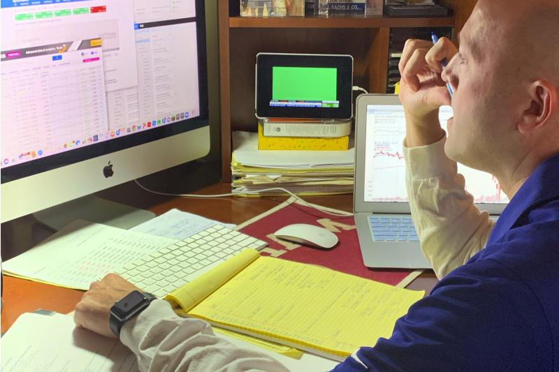 In this image provided by Jay Woods,  Woods, a Designated Market Maker with IMC and NYSE Floor Governor, who normally works on the New York Stock Exchange trading floor, works in his home office in Basking Ridge, N.J., Thursday, March 26, 2020.  Stocks are opening lower on Wall Street, Friday, March 27,  as the market gives back some of the gains it piled up over the past three days.  (Shannon Woods/Courtesy Jay Woods via AP)