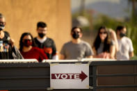 FILE - In this Tuesday, Nov. 3, 2020 file photo, Voters stand in line outside a polling station, on Election Day, Tuesday, Nov. 3, 2020, in Mesa, Ariz. County election officials throughout Arizona have found less than 200 cases of potential voter fraud from the 2020 presidential election that require review by local prosecutors, according to an Associated Press investigation. (AP Photo/Matt York, File)