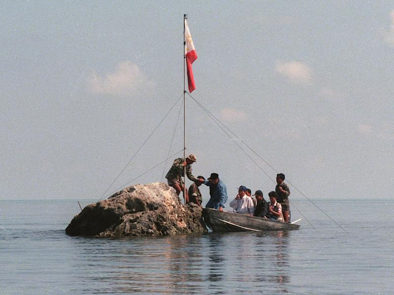 A team of navy personnel and three Philippine congressmen standing on a tiny rock in the Scarborough Shoal with a Filipino flag in protest at Chinese land grabbing: AFP/Getty Images