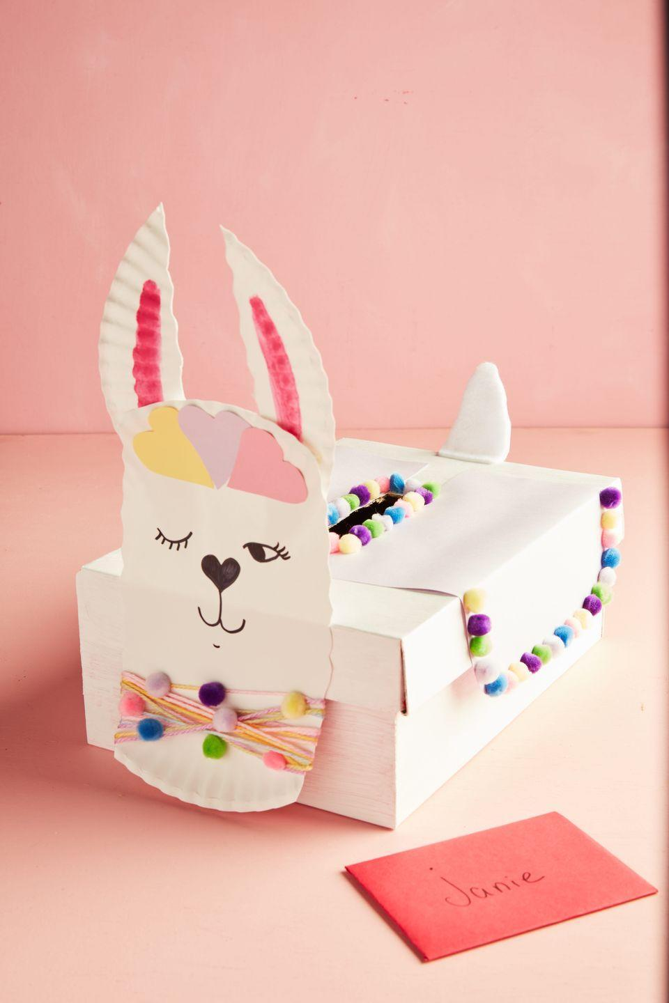 "<p>A wink and a smile welcome candy and cards to this sweet llama Valentine's box.</p><p><strong>To make:</strong> Wrap a <a href=""https://www.amazon.com/Factory-Direct-Craft-Decorate-Rectangle/dp/B00CMB8TCQ/ref=sr_1_44"" rel=""nofollow noopener"" target=""_blank"" data-ylk=""slk:papier-mâché box"" class=""link rapid-noclick-resp"">papier-mâché box</a> in white craft paper. Cut a slit in the top of the box. Add a saddle made from white office paper on either side of the slit. Decorate around the slit and along the bottom of the saddle with <a href=""https://www.amazon.com/Caydo-Pieces-Pompoms-Creative-Decorations/dp/B07S4MYG5Y/ref=sr_1_1_sspa"" rel=""nofollow noopener"" target=""_blank"" data-ylk=""slk:mini pom-poms"" class=""link rapid-noclick-resp"">mini pom-poms</a>, adhering them with hot glue. To create the face, cut two strips off opposite sides of a white paper plate. Color the center of the strips with a pink marker; adhere to the back of the plate to create the ears. Decorate the face with paper hearts. Draw on eyes, a heart-shaped nose, and mouth with black marker, and add yarn and mini pom-poms to create a ""collar""; adhere to the front of the box. Cut out a tail from white craft foam and attach to the back of the box with hot glue.</p><p><a class=""link rapid-noclick-resp"" href=""https://www.amazon.com/Sheets-Better-Office-Products-Crafts/dp/B089DT3TC9/ref=sr_1_3?tag=syn-yahoo-20&ascsubtag=%5Bartid%7C10050.g.25844424%5Bsrc%7Cyahoo-us"" rel=""nofollow noopener"" target=""_blank"" data-ylk=""slk:SHOP CRAFT FOAM"">SHOP CRAFT FOAM</a></p>"