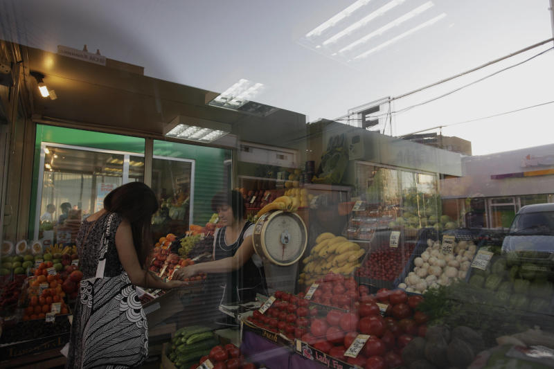 A customer and a seller seen through the window of a street side market shop in Moscow, Russia, on Tuesday, May 31, 2011. A massive and unprecedented outbreak of bacterial infections linked to contaminated vegetables claimed two more lives in Europe on Tuesday. Russia's chief sanitary agency on Monday banned the imports of cucumbers, tomatoes and fresh salad from Spain and Germany pending further notice. (AP Photo/Alexander Zemlianichenko Jr)