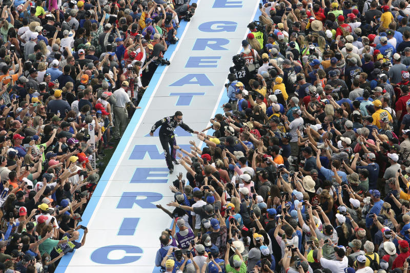 Jimmie Johnson greets fans during driver introductions before the NASCAR Daytona 500 auto race at Daytona International Speedway, Sunday, Feb. 16, 2020, in Daytona Beach, Fla. (AP Photo/David Graham)