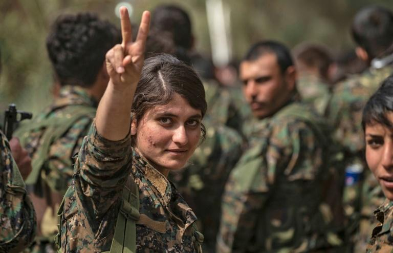 Fighters of the Kurdish-led Syrian Democratic Forces, women prominent among them, celebrate victory after nearly five years of fighting the most brutal jihadist group in modern history