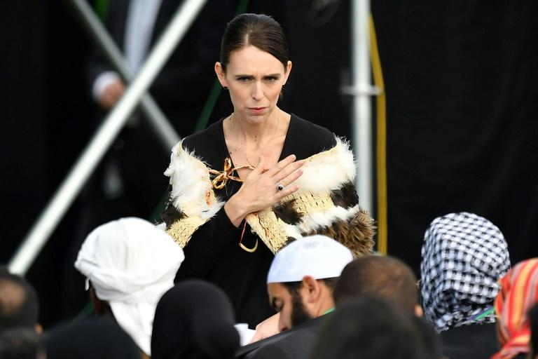 Prime Minister of New Zealand Jacinda Ardern places her hand over her heart as she walks past a family who lost members in the mosque attacks of 2019 (AFP Photo/Marty MELVILLE)