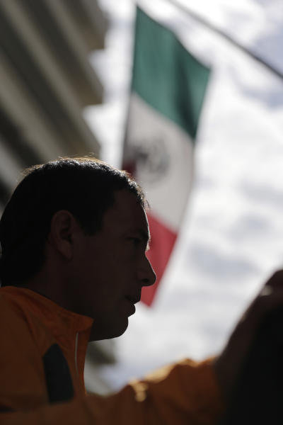 Cyclist Carlos Gutierrez, a double amputee, is silhouetted against the Mexico flag during a stop at the Mexican Consulate, Thursday, Nov. 7, 2013, in San Antonio. Gutierrez, a Mexican asylum seeker who fled to the U.S. after extortionists cut his legs off for not paying the extortion fees, is riding his bike from El Paso, Texas to Austin, Texas, to raise awareness on the situation of political asylum seekers. (AP Photo/Eric Gay)
