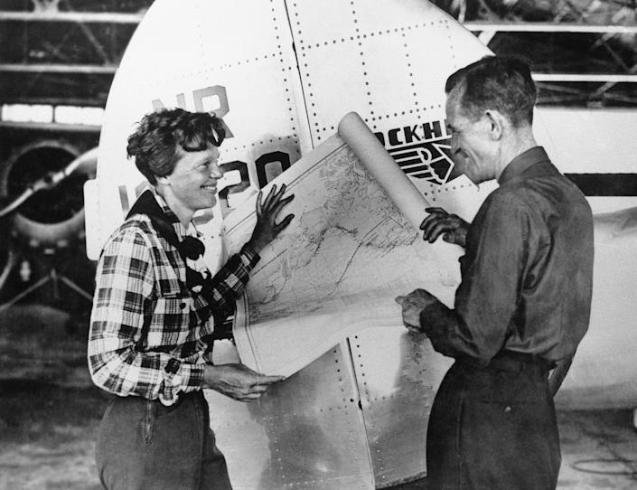 FILE - In this undated photo, Amelia Earhart, left, and navigator Fred Noonan pose with a map of the Pacific showing route of their last flight in this undated photo. A $2.2 million expedition that hoped to find wreckage from famed aviator Amelia Earhart's final flight is on its way back to Hawaii without the dramatic, conclusive plane images searchers were hoping to attain. But the group leading the search, The International Group for Historic Aircraft Recovery, still believes Earhart and her navigator crashed onto a reef off a remote island in the Pacific Ocean 75 years ago this month, its president told The Associated Press on Monday, July 23, 2012. (AP Photo, File)