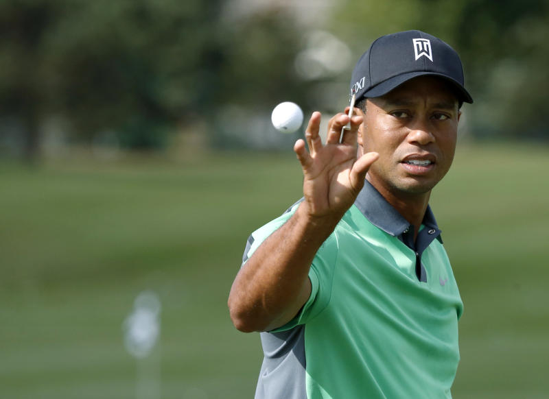 Tiger Woods catches a ball on the driving range from his caddie during the first round of the BMW Championship golf tournament at Conway Farms Golf Club in Lake Forest. Ill., Thursday, Sept. 12, 2013. (AP Photo/Charles Rex Arbogast)