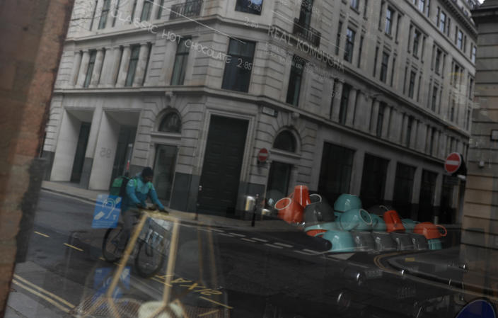 "A Deliveroo worker cycles past a closed coffee shop near Guildhall in the City of London, Tuesday, April 6, 2021. When the pandemic struck, about 540,000 workers vanished from London's financial hub almost overnight. The area known as ""the City"" became a ghost town as many people began working from home. A year on, most haven't returned to the business hub. (AP Photo/Alastair Grant)"