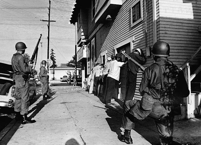 Armed National Guardsmen force a line of Black men to stand against the wall of a building during the Watts riots in 1965 | Hulton Archive/Getty Images