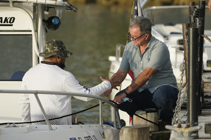 Ramon Saul Sanchez, right, leader of the nonprofit group Movimiento Democracia that launched several flotillas in the past, shakes hands with boater Alain Dennes before Dennes departs, Friday, July 23, 2021, in downtown Miami. A small group of Cuban Americans launched motorboats from Miami to their homeland to show support for people experiencing hardships on the island. Five boats left the Bayside marina just before 8 a.m. Friday. They plan to refuel in Key West before heading into the Florida Straits. (AP Photo/Wilfredo Lee)