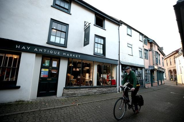 """A man cycles past closed shops in Hay-on-Wye with Wales under a two-week """"firebreak"""" lockdown (Nick Potts/PA)"""