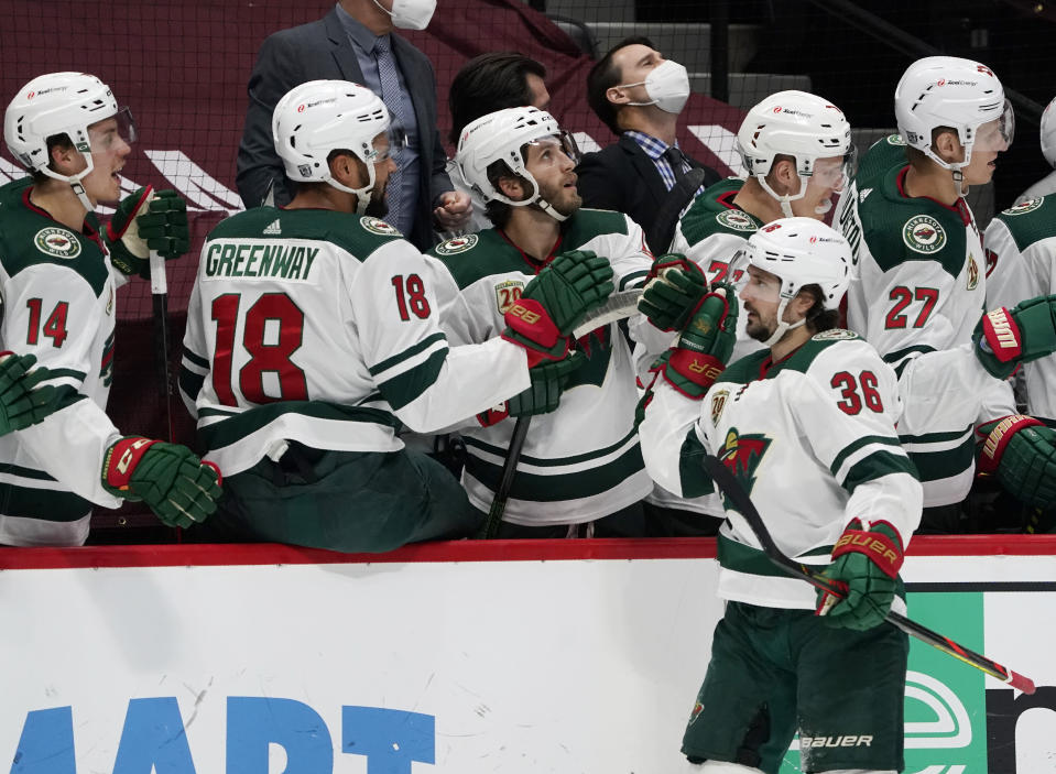 Minnesota Wild right wing Mats Zuccarello, front, is congratulated as he passes the team box after scoring a goal against the Colorado Avalanche in the first period of an NHL hockey game Wednesday, Feb. 24, 2021, in Denver. (AP Photo/David Zalubowski)