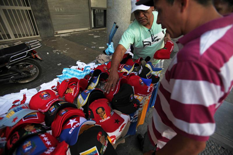"A street vendor sells baseball caps decorated with images of Venezuela's late President Hugo Chavez, and T-shirts with a the words in Spanish ""I am Chavez"" in Caracas, Venezuela, Monday, March 11, 2013. At Caracas's choked Bolivar Plaza, a favorite hangout for the late president's supporters, shoppers can find virtually anything Chavez-related the mind can dream up. (AP Photo/Fernando Llano)"
