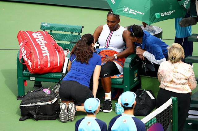 Serena Williams talks with medical staff before retiring from her match against Garbine Muguruza with a viral illness in the third round of the Indian Wells WTA tournament (AFP Photo/CLIVE BRUNSKILL)