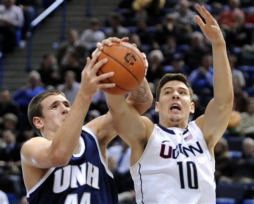 CORRECTS DATELINE TO HARTFORD Connecticut's Tyler Olander, right, and New Hampshire's Chris Pelcher fight for a loose ball during the first half of an NCAA college basketball game in Hartford, Conn., Thursday, Nov. 29, 2012. (AP Photo/Fred Beckham)