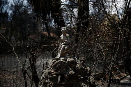A fountain is seen in yard of a burnt house following a wildfire in the village of Mati, near Athens