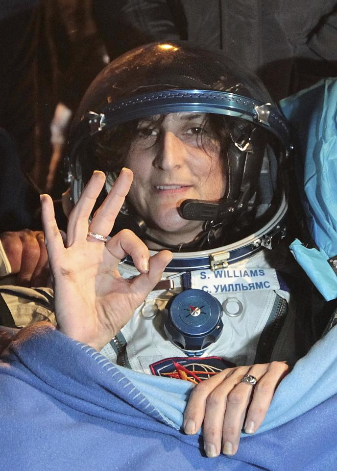 International Space Station crew member U.S. astronaut Sunita Williams gestures shortly after landing in a Soyuz capsule outside the town of Arkalyk, Kazakhstan, Monday, Nov. 19, 2012. Three astronauts, NASA's Williams, Russian astronaut Yury Malenchenko and Aki Hoshide of Japan's JAXA space agency, touched down in the dark, chilly expanses of central Kazakhstan onboard a Soyuz capsule Monday after a 125-day stay at the International Space Station. (AP Photo/Maxim Shipenkov, Pool)