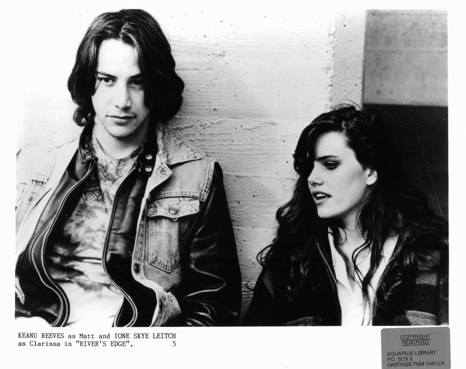 Keanu Reeves stands against a wall with Ione Skye in a scene from the film 'River's Edge', 1986.