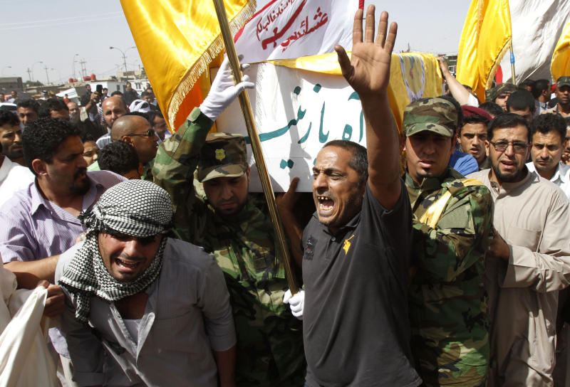 "FILE - In this Friday, May 17, 2013 file photo, Iraqi mourners carry a coffin containing a Shiite fighter killed in Syria, with Arabic that reads, ""O, Zeinab,"" during a funeral in Basra, Iraq's second-largest city, 340 miles (550 kilometers) southeast of Baghdad, Iraq. Iraqi Shiite fighters are playing an increasingly prominent role in neighboring Syria's civil war, exacerbating Iraq's own fraught sectarian tensions even as violence in the country spikes to its highest level in years. (AP Photo/ Nabil Al-Jurani, File)"