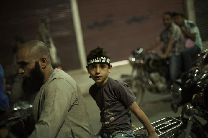 An Egyptian Muslim child rides on the back of a motorbike during a rally supporting former President Mohammed Morsi in Assiut, Upper Egypt, Tuesday, Aug. 6, 2013. Islamists may be on the defensive in Cairo, but in Egypt's deep south they still have much sway and audacity: over the past week, they have stepped up a hate campaign against the area's Christians. Blaming the broader Coptic community for the July 3 coup that removed Islamist President Mohammed Morsi, Islamists have marked Christian homes, stores and churches with crosses and threatening graffiti. (AP Photo/Manu Brabo)