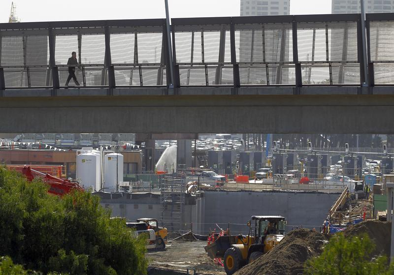 A pedestrian walks over a large construction project for U.S. Customs at the San Ysidro border crossing into the United States in San Ysidro, California