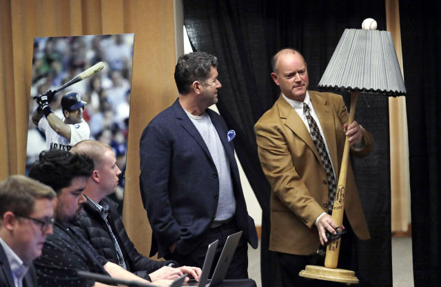 "Former Seattle Mariners designated hitter Edgar Martinez, center, watches as Tim Hevly, Mariners vice president of communications, brings in a ""light bat"" to start a news conference Tuesday, Jan. 29, 2019, in Seattle. Martinez, who used the baseball bat-themed lamp in a television commercial during his playing days, was elected to baseball's Hall of Fame a week earlier. (AP Photo/Elaine Thompson)"