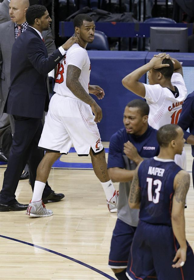 Cincinnati guard Sean Kilpatrick, top left, leaves the court as Connecticut guard Shabazz Napier (13) celebrates with teammates after an NCAA college basketball game in the semifinals of the American Athletic Conference men's tournament Friday, March 14, 2014, in Memphis, Tenn. Kilpatrick missed a layup in the final seconds as Connecticut won 58-56. (AP Photo/Mark Humphrey)