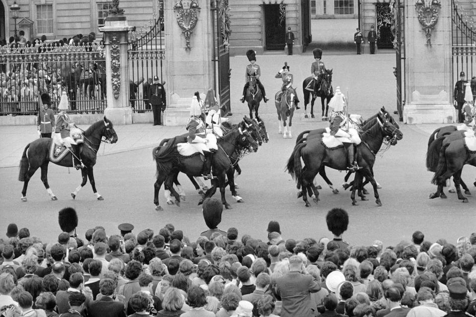 FILE - In this file photo dated June 13, 1964, Britain's Queen Elizabeth II and Prince Philip, left, take the salute as the Sovereign Escort of the Household Cavalry ride past Buckingham Palace in London. The ceremony marked the Queen's official birthday, her 38th, and the Colour trooped was that the First Battalion of the Coldstream Guards. Prince Philip who died Friday April 9, 2021, aged 99, lived through a tumultuous century of war and upheavals, but he helped forge a period of stability for the British monarchy under his wife, Queen Elizabeth II. (AP Photo, FILE)