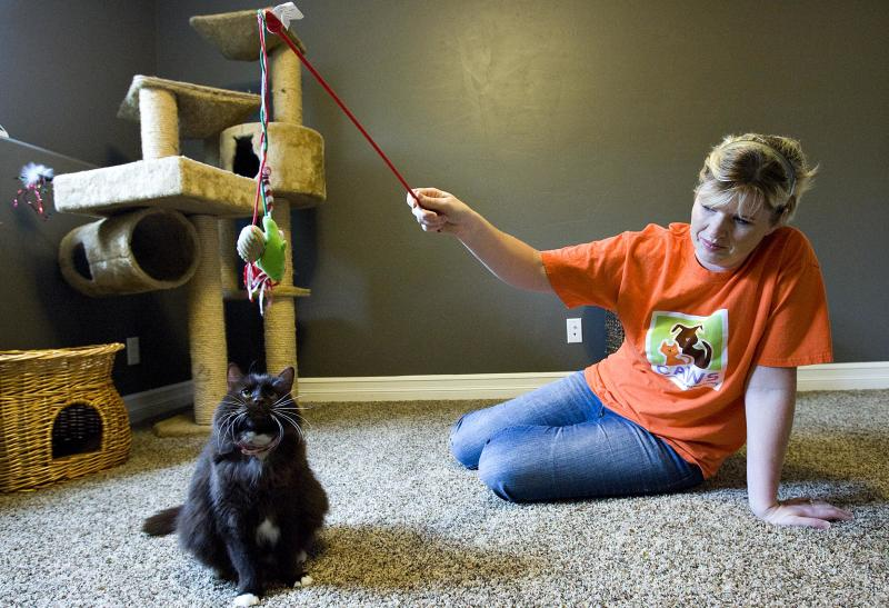 Janita Coombs plays with her cat, Andrea, at her Syracuse, Utah home, on Sunday, Oct. 16, 2011. The Utah city may put an end to its gas chamber after  Andrea survived a shelter's two attempts to euthanize her.  Animal shelter volunteers are expected to appear at a West Valley City Council meeting Tuesday evening to make the case for using lethal injections instead.  Andrea had not been adopted for 30 days when shelter officials tried to put her to death in October. She survived, so they gassed her again.  Shelter officials presumed she was dead when they put her in a plastic bag in a cooler. She was later found alive.   (AP Photo/The Salt Lake Tribune, Djamila Grossman)