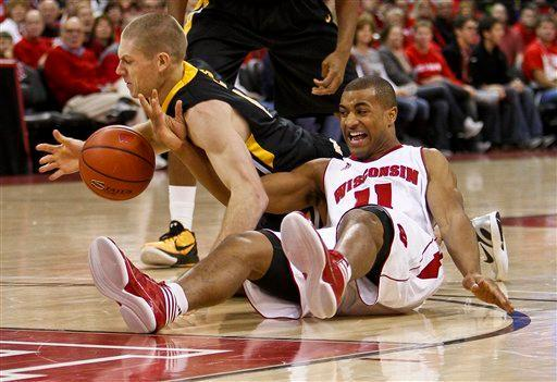 Iowa's Matt Gatens, left, and Wisconins' Jordan Taylor battle for a loose ball during the first half of an NCAA college basketball game Saturday, Dec. 31, 2011, in Madison, Wis. (AP Photo/Andy Manis)