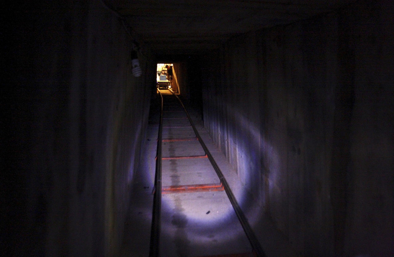 A soldier looks into a tunnel found under the Mexico-U.S. border in Tijuana November 30, 2011. Police discovered the tunnel running to California from Mexico and authorities from both countries seized more than 32 tons of marijuana. The tunnel is equipped with a hydraulic entry, an elevator and electric rail cars, according to a statement released by the U.S. Immigration and Customs Enforcement. REUTERS/Jorge Duenes (MEXICO - Tags: CRIME LAW DRUGS SOCIETY)