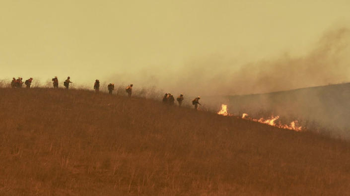 In this photo provided by the Santa Barbara County Fire Department, a hand crew works on a hill to extinguish a fire Tuesday, Oct. 12, 2021, in Goleta, Calif. (Mike Eliason/Santa Barbara County Fire Department via AP)