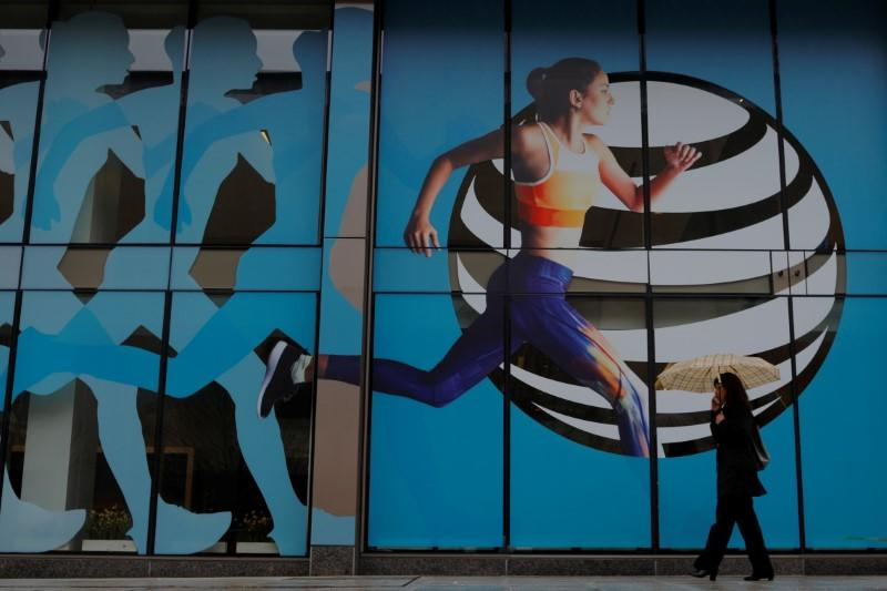 A pedestrian walks past an AT&T store in Boston