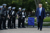 FILE - In this June 1, 2020 file photo, President Donald Trump walks past police in Lafayette Park after visiting outside St. John's Church across from the White House in Washington. An internal investigation has determined that the decision to clear racial justice protestors from an area in front of the White House last summer was not influenced by then-President Donald Trump's plans for a photo opportunity at that spot. The report released Wednesday by the Department of Interior's Inspector General concludes that the protestors were cleared by U.S. Park Police on June 1 of last year so new fencing could be installed. (AP Photo/Patrick Semansky)