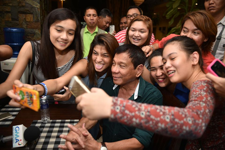 FILE PHOTO: Philippine President Rodrigo Duterte poses for selfie pictures with supporters in Mindanao on May 15, 2016. (Photo: TED ALJIBE/AFP via Getty Images)