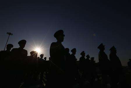 Military delegates are silhouetted as they arrive at Tiananmen Square