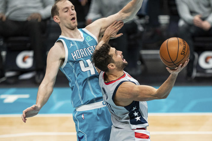 Washington Wizards guard Raul Neto, right, drives to the basket while guarded by Charlotte Hornets center Cody Zeller (40) during the first half of an NBA basketball game in Charlotte, N.C., Sunday, Feb. 7, 2021. (AP Photo/Jacob Kupferman)