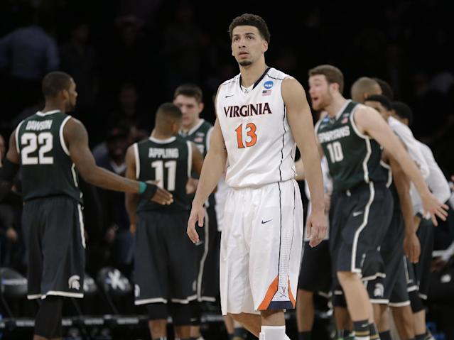 Virginia's Anthony Gill leaves the court as Michigan State players celebrate a 61-59 win over Virginia in a regional semifinal of the NCAA men's college basketball tournament, Saturday, March 29, 2014, in New York. (AP Photo/Seth Wenig)