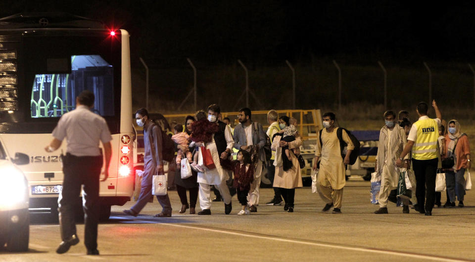 Afghan evacuees are directed to buses after their arrival by a plane at Skopje International Airport, North Macedonia, late Monday, Aug. 30, 2021. A first group of 149 Afghan evacuees landed late Monday in North Macedonia, where they will stay for a few months pending resettlement elsewhere. (AP Photo/Boris Grdanoski)