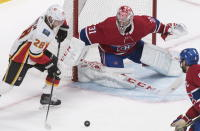 Calgary Flames' Elias Lindholm (28) moves in on Montreal Canadiens goaltender Carey Price as Canadiens' Shea Weber defends during second period NHL hockey action in Montreal, Monday, Jan. 13, 2020. (Graham Hughes/The Canadian Press via AP)