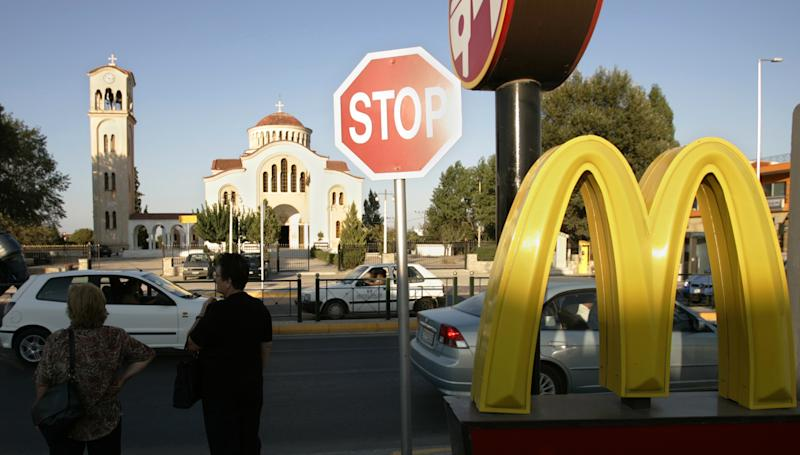 FILE - In this Aug. 19, 2004 file photo, commuters stand near a McDonald's restaurant in Marathon, Greece.  McDonald's Corp. says a key revenue figure came in flat in July as diners pulled back amid a persistently weak economy. After years of outperforming rivals by emphasizing value and rolling out popular new items, the stall is also a sign that competition is intensifying for the world's biggest hamburger chain. The figure dipped 0.6 percent in Europe because of weakness in Germany and several Southern European markets. It fell 1.5 percent in the Asia Pacific, Middle East and Africa region, a key growth area for McDonald's. (AP Photo/Lefteris Pitarakis)