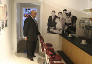 Rodney Hurst visits a replica of the lunch counter where he took part in a peaceful demonstration to protest the discrimination faced by Blacks, at a display at at the Ritz Theater, on Friday, Oct. 23, 2020, in Jacksonville, Fla. In the background is a blow up of a photo taken in 1960 when he was 16. After leaving the lunch counter in downtown Jacksonville as a teen, a mob of whites began indiscriminately clubbing African Americans with baseball bats and ax handles during a day now remembered as Ax Handle Saturday. (AP Photo/Bobby Caina Calvan)
