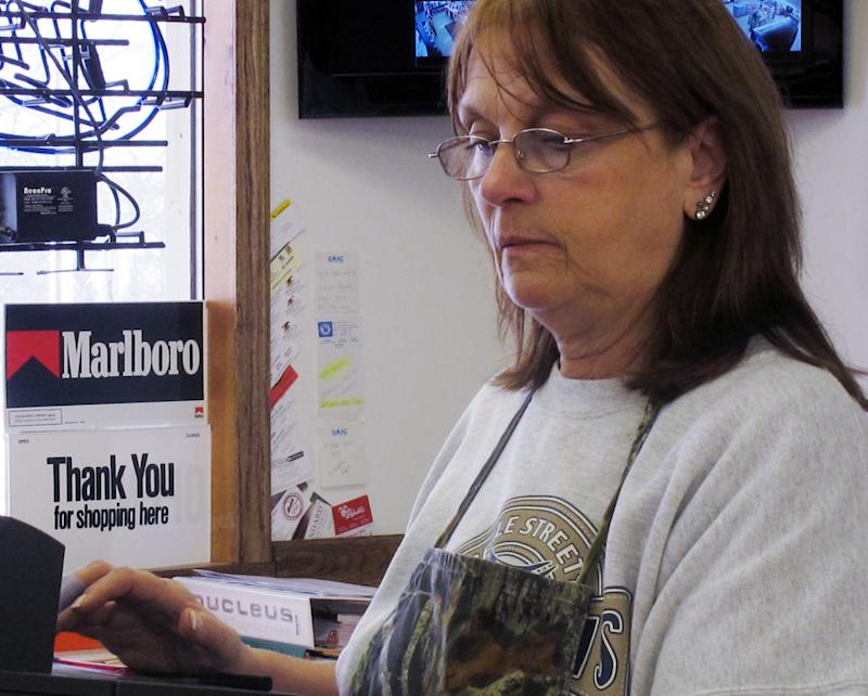 In this Feb. 27, 2013 photo, clerk Debi Wilson uses the cash register at Two Rivers Market near the Tyson Foods hog-processing plant in Columbus Junction, Iowa.  Wilson said she hopes that federal budget cuts do not require the temporary shutdown of the Tyson plant  whose employees make up the majority of her customers. (AP Photo/Ryan J. Foley)