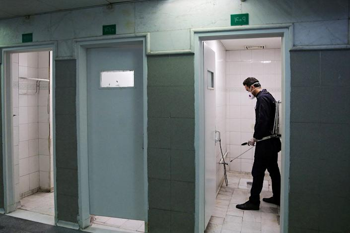 A member of a medical team sprays disinfectant to sanitize bathrooms in Imam Reza's holy shrine, following the coronavirus outbreak, in Mashhad, Iran on February 27, 2020.