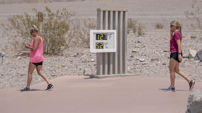Visitors walk past the thermometer at the Furnace Creek Visitor Center in Death Valley, California, U.S., on Thursday, June 17, 2021.(Kyle Grillot/Bloomberg via Getty Images)