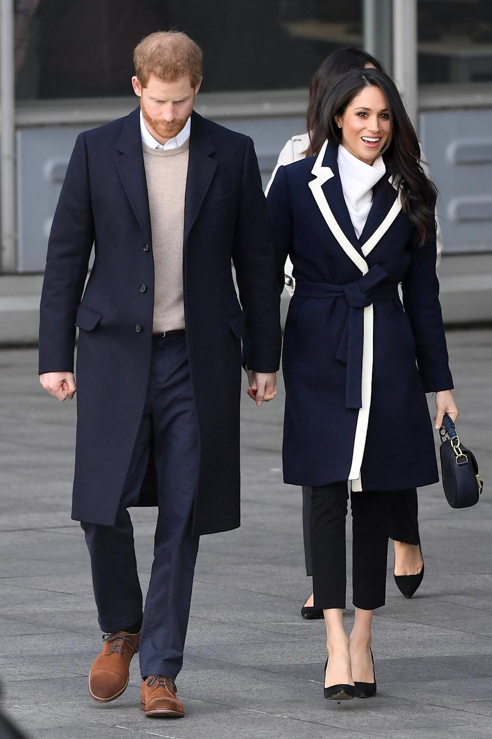 <p>Markle opted for a navy coat with white detail by J. Crew and matching white cowl neck sweater for a visit to Birmingham in March 2018. <em>(Image via Getty Images)</em></p>