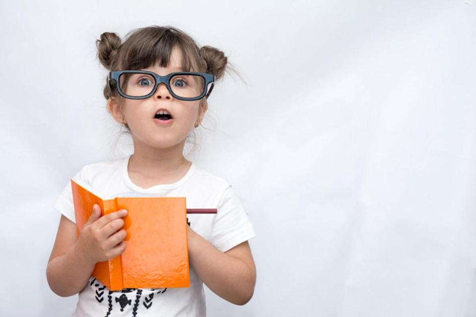 Child wearing glasses, writing in notebook using pencil, keeping mouth wide open.