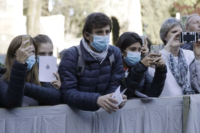 People wear surgical masks as they wait for the arrival of Pope Francis outside the Santa Sabina Basilica on Ash Wednesday