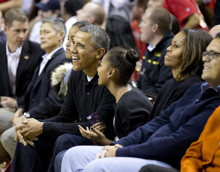 President Barack Obama, center, with first lady Michelle Obama, right, and their daughters Sasha, left, of Pres. Obama, and Malia and mother-in-law Marian Robinson, cheer as they watch a basketball game between his brother-in-law Oregon State Beavers Coach Craig Robinson's team play against the Maryland Terrapins, Sunday, Nov. 17, 2013, at the Comcast Center in College Park, Md., to watch his (AP Photo/Manuel Balce Ceneta)