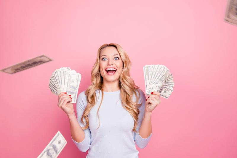 Woman holding money and smiling.